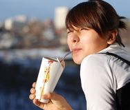 Portrait of young girl. The young girl in a white blouse drinks juice on a balcony royalty free stock images