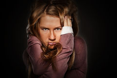 Portrait of a young girl. Closeup portrait of beautiful young long-haired serious girl on a black background Stock Photos