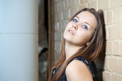 Portrait of young girl with against brick wall Royalty Free Stock Photo