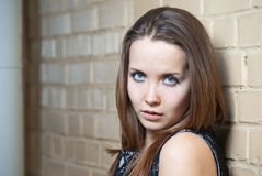 Portrait of young girl with against brick wall Stock Image