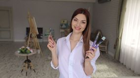 Portrait of a talented girl artist in the studio. Portrait of a young girl artist with long dark hair with paintbrushes in hand. Portrait of a talented girl stock footage