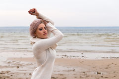 Portrait of a young girl at the autumn beach. Portrait of a young girl in white sweater at the autumn beach Royalty Free Stock Images