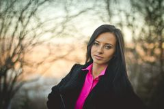 Portrait of a young girl in the autumn forest at sunset. Pink shirt stock photo