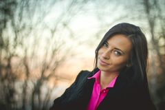 Portrait of a young girl in the autumn forest at sunset. Pink shirt royalty free stock photography