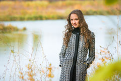 Portrait of a young girl on a background of the autumn river Royalty Free Stock Images