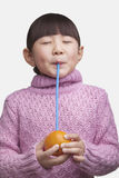 Portrait of young girl with bangs and eyes closed drinking an orange with a straw, studio shot Stock Photo