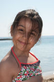 Young girl at the beach. A young girl smiling at the beach Royalty Free Stock Photography