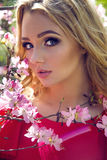 Portrait of a young girl blondes with make-up. In the cherry Sakura pink white in a white skirt and pink top Royalty Free Stock Images
