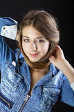 Portrait young girl in a blue jeans jacket in dark studio Stock Image