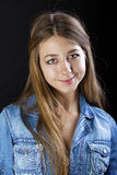 Portrait young girl in a blue jeans jacket in dark studio Royalty Free Stock Images