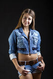 Portrait young girl in a blue jeans jacket in dark studio Royalty Free Stock Photo