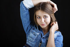 Portrait young girl in a blue jeans jacket in dark studio Royalty Free Stock Photos