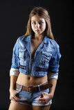 Portrait young girl in a blue jeans jacket and shorts in dark st Stock Photos