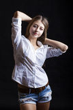 Portrait young girl in a blue jeans jacket and shorts in dark st Royalty Free Stock Image