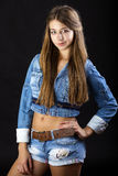 Portrait young girl in a blue jeans jacket and shorts in dark st Royalty Free Stock Photography