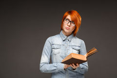 Portrait of young girl with book over grey background. Copy spac Stock Images