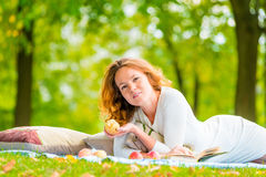 Portrait of young girl with books and apple. On the plaid in the park Royalty Free Stock Image