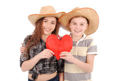 Portrait of young girl and boy holding a red heart shaped pillow. Isolated on white Stock Image