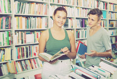 Portrait of young girl and boy taking new books. Together in shop Stock Photo