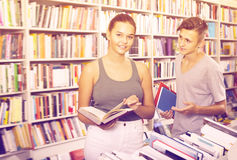 Portrait of young girl and boy taking new books. Together in shop Royalty Free Stock Photos