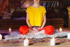 Portrait of a young girl in bright clothes practicing meditation in a crafting room surrounded by candles. Newage stock photography