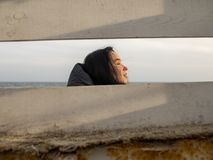 Portrait of a young girl with brown hairs view through a wooden fence on the background of the sea stock photography