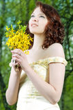 Portrait of young girl with bunch of flowers Royalty Free Stock Photo
