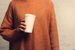Portrait of a young girl with a coffee cup in hand. Coffee cup close-up. Warm color filter. The blank for your ideas Royalty Free Stock Photography