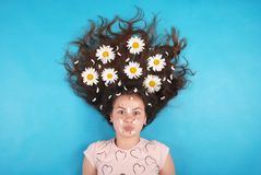 Portrait of a young girl with daisies in their hair lying on the floor royalty free stock photo