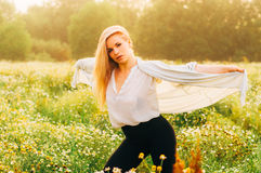 Portrait of young girl dancing in chamomile field Stock Photo