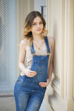 Portrait of a young girl in denim overalls Stock Images
