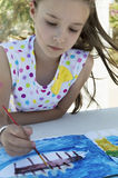 Portrait of a young girl drawing a picture outdoors Stock Photo