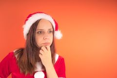 Portrait of a young girl dressed as Santa Claus on orange background. Happy New year and merry Christmas! royalty free stock photography