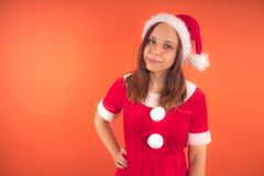 Portrait of a young girl dressed as Santa Claus on orange background. Happy New year and merry Christmas! stock photography