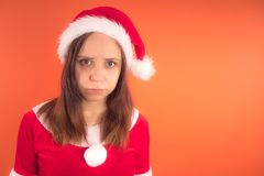 Portrait of a young girl dressed as Santa Claus on orange background. Happy New year and merry Christmas! stock images