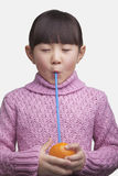 Portrait of young girl drinking an orange with a straw, studio shot Stock Image