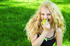 Portrait of young girl eating green apple Stock Image