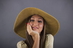 Portrait of young girl in fashion dress with hat sitting chair Royalty Free Stock Photos