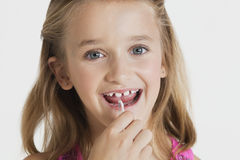 Portrait of young girl flossing teeth against gray background Royalty Free Stock Image