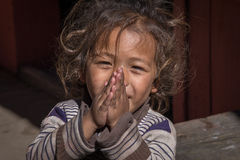 Portrait young girl with folded hands in street, Nepal. Close up Stock Photography