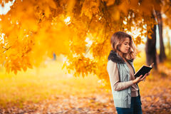 Portrait of a young girl in fur vest and reading book on background autumn park Royalty Free Stock Image