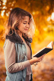 Portrait of a young girl in fur vest and reading book on background autumn park Royalty Free Stock Images