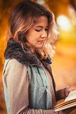 Portrait of a young girl in fur vest and reading book on background autumn park Stock Photography