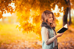 Portrait of a young girl in fur vest and reading book on background autumn park Stock Photo