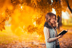 Portrait of a young girl in fur vest and reading book on background autumn park Royalty Free Stock Photos