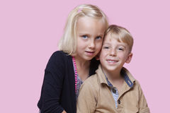 Portrait of young girl with happy brother over pink background Royalty Free Stock Image