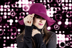 Portrait of young girl with a hat in front of spotlights backgro Royalty Free Stock Image