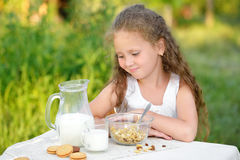 Portrait of young girl having breakfast and drinking milk outdoor. Cereal, healthy lifestyle. Portrait of young girl sitting near the table and having breakfast Stock Photo