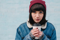 Portrait of a young girl hipster heated coffee and smiling. Portrait of a young girl hipster blue denim jacket and hat, warmed coffee and smiling on a light blue Stock Photo