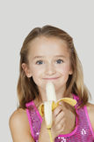 Portrait of young girl holding banana against gray background Stock Photos